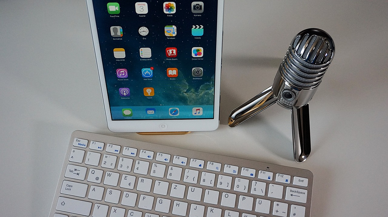 Podcast set up with keyboard, microphone and tablet