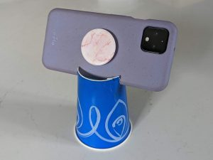 A phone tripod made out of a cardboard cup.